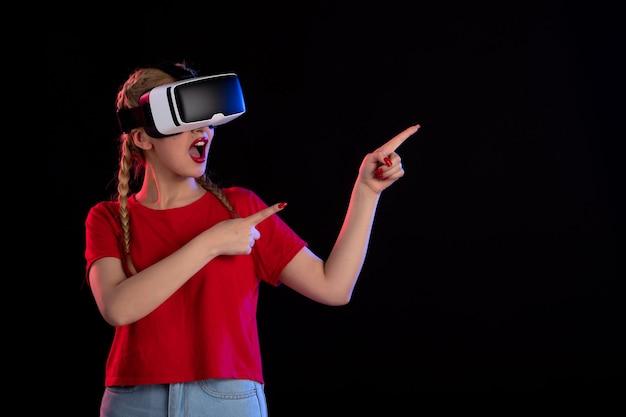 Vue de face d'une jolie femme jouant à la réalité virtuelle dans l'obscurité