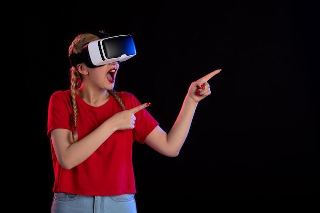 Vue de face d'une jolie femme jouant à la réalité virtuelle sur une fantaisie de jeu à ultrasons sombre