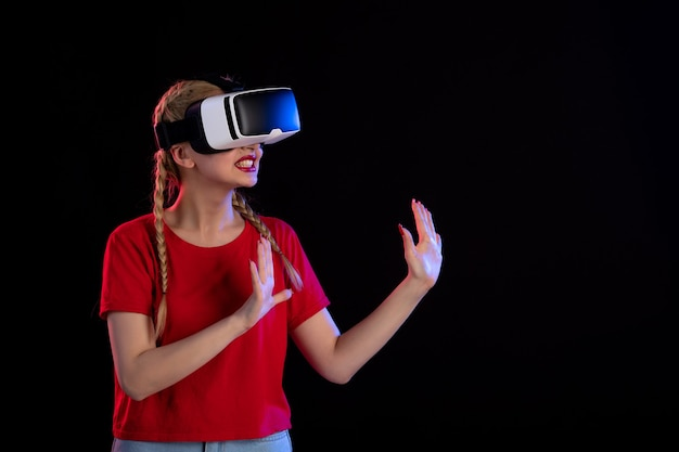 Vue de face d'une jolie femme jouant à la réalité virtuelle sur le visuel de jeux fantastiques à ultrasons sombres