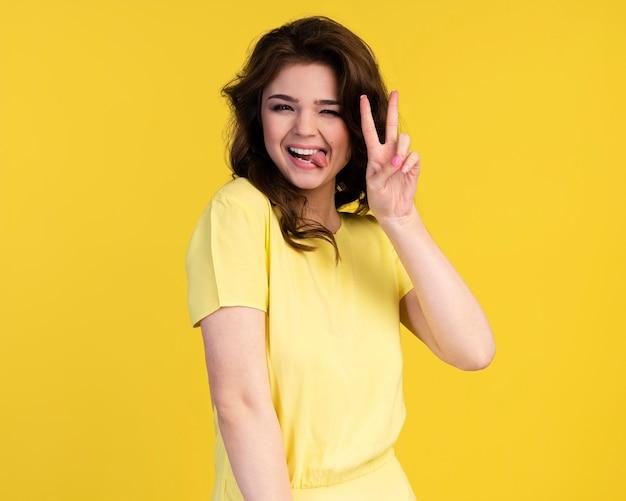Vue de face de jolie femme avec langue et signe de paix