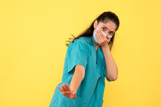 Vue de face de la jolie femme médecin avec masque médical couvrant sa bouche sur mur jaune