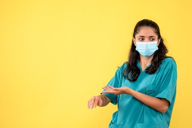 Vue de face de la jolie femme médecin avec masque médical vérifier l'heure sur le mur jaune