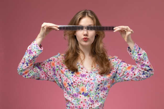 Vue de face jolie femme montre une bande de film horizontalement