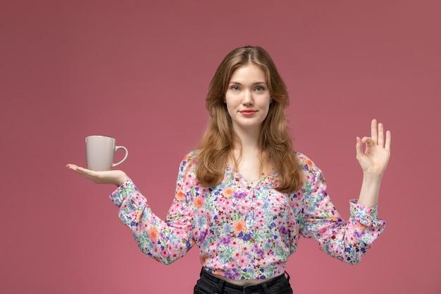 Vue de face jolie femme montre que tout va bien avec sa tasse