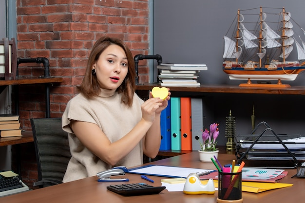 Vue de face d'une jolie femme pointant sur du papier en forme de coeur au bureau
