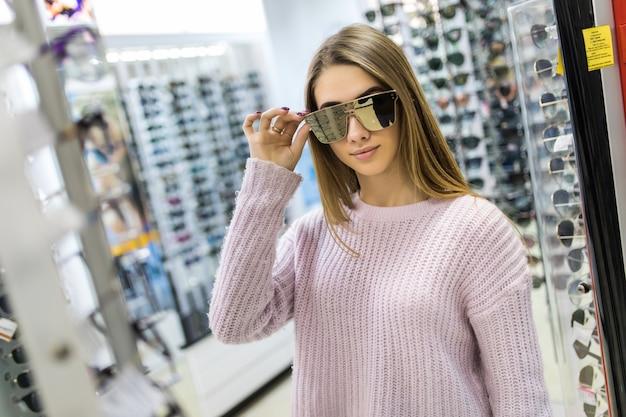 Vue de face de jolie femme en pull blanc essayer des lunettes en magasin professionnel sur