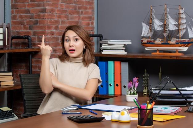 Vue de face d'une jolie femme surprenante avec une idée travaillant au bureau
