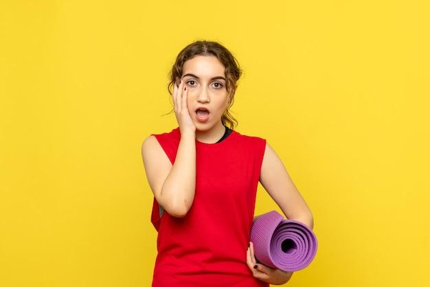 Vue de face de jolie femme avec tapis violet sur mur jaune