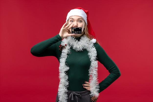 Vue de face jolie femme tenant une carte bancaire noire sur fond rouge