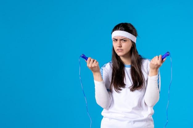 Vue de face jolie femme tenant la corde à sauter sur bleu