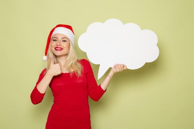 Vue de face jolie femme tenant grand panneau blanc sur le mur vert noël neige photo vacances émotion nouvel an