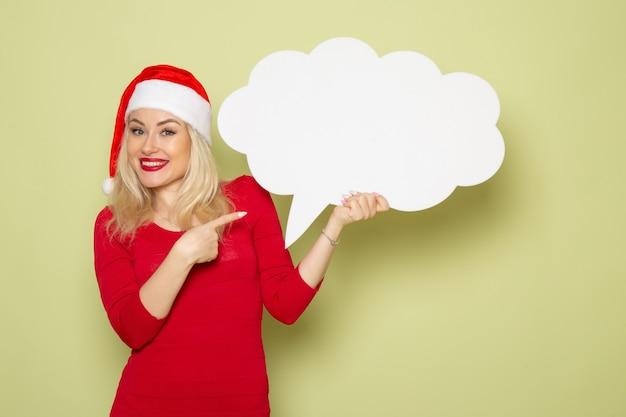 Vue de face jolie femme tenant grand panneau blanc sur mur vert nouvel an vacances neige photo noël émotion