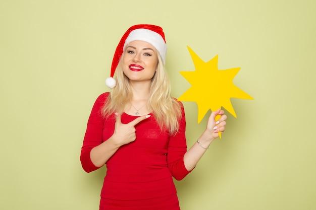 Vue de face jolie femme tenant grosse figure jaune sur le mur vert couleur vacances émotions neige nouvel an noël