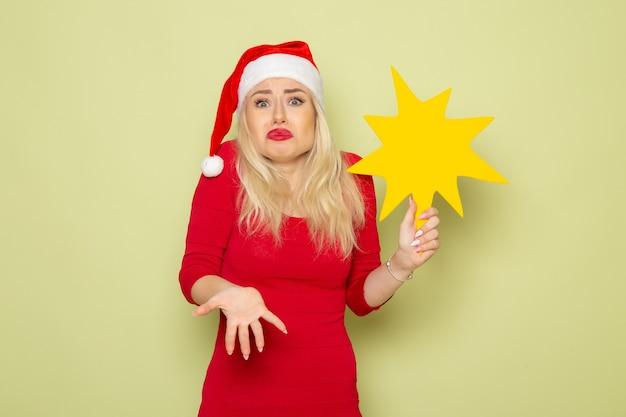 Vue de face jolie femme tenant grosse figure jaune sur mur vert émotion neige nouvel an vacances couleur