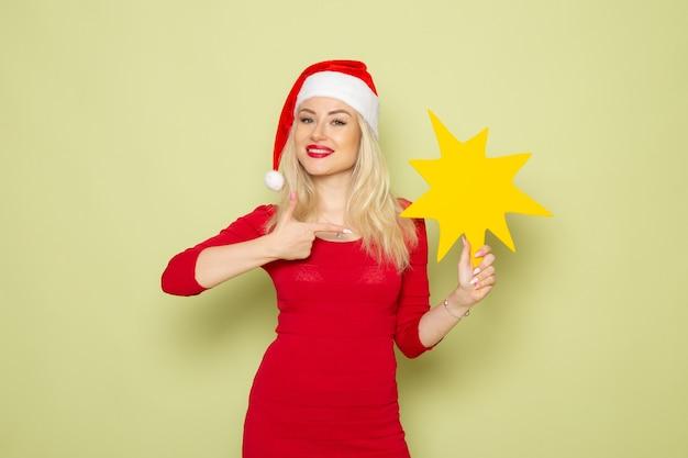 Vue de face jolie femme tenant grosse figure jaune sur le mur vert noël émotion neige nouvel an vacances couleur