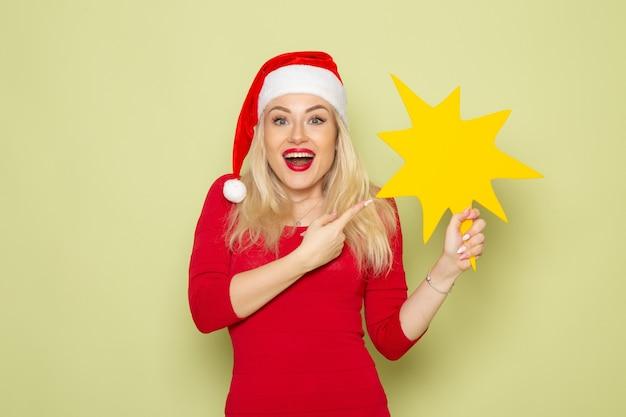 Vue de face jolie femme tenant grosse figure jaune sur mur vert vacances émotion neige nouvel an noël