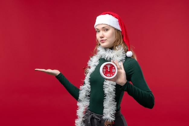 Vue de face jolie femme tenant une horloge sur un bureau rouge