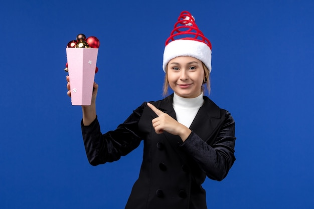 Vue de face jolie femme tenant des jouets d'arbre en plastique sur mur bleu vacances de nouvel an bleu