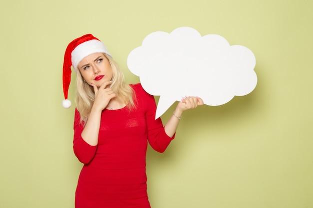 Vue de face jolie femme tenant un panneau blanc en forme de nuage sur le mur vert photo neige de noël vacances nouvel an