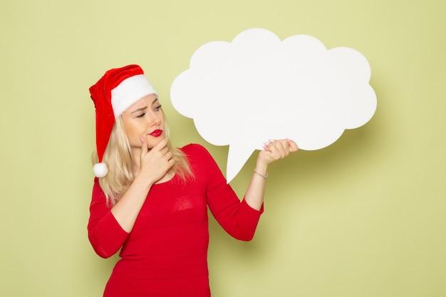 Vue de face jolie femme tenant un panneau blanc en forme de nuage sur le mur vert vacances émotions photo de noël neige du nouvel an