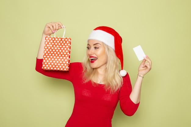 Vue de face jolie femme tenant présent dans petit paquet et carte bancaire sur mur vert neige émotion vacances noël nouvel an couleur