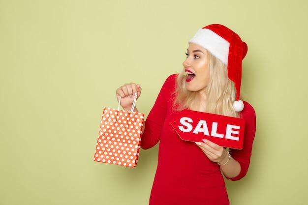 Vue de face jolie femme tenant présent et vente écrit sur mur vert neige émotion vacances noël nouvel an couleur