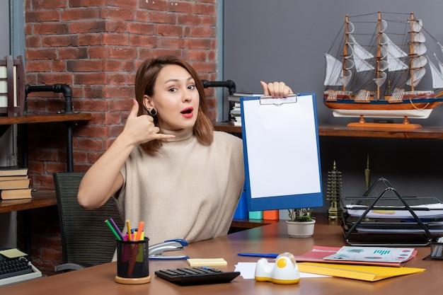 Vue de face d'une jolie femme tenant un presse-papiers en train de m'appeler au bureau