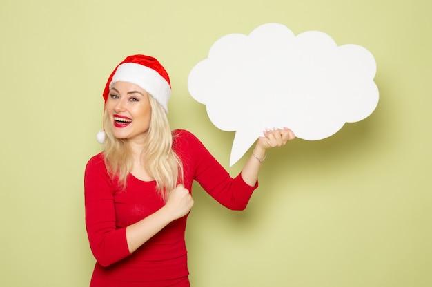 Vue de face jolie femme tenant signe blanc en forme de nuage sur le mur vert émotion neige nouvel an vacances noël