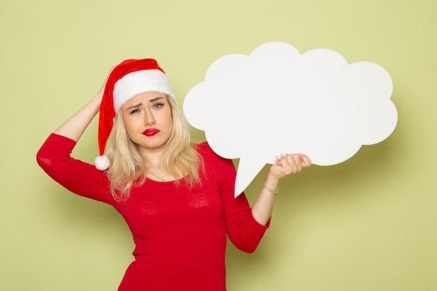 Vue de face jolie femme tenant signe blanc en forme de nuage sur le mur vert noël neige vacances émotion nouvel an