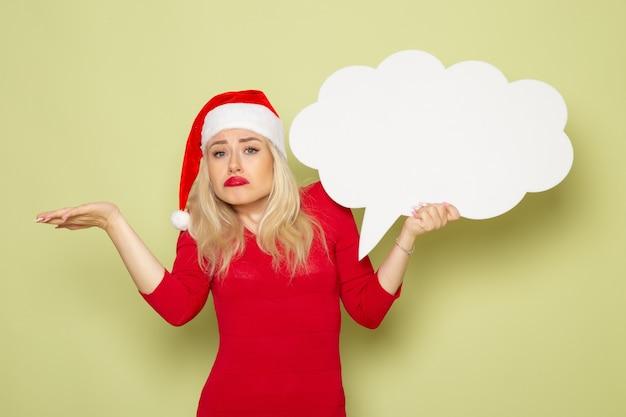 Vue de face jolie femme tenant signe blanc en forme de nuage sur le mur vert vacances émotion photo de noël neige du nouvel an