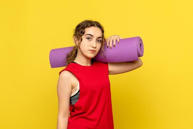 Vue de face de la jolie femme tenant tapis violet sur jaune