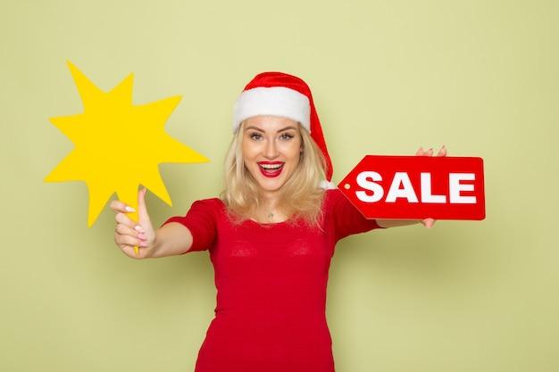 Vue de face jolie femme tenant vente écrit et grande figure jaune sur le mur vert neige émotion vacances noël nouvel an couleur