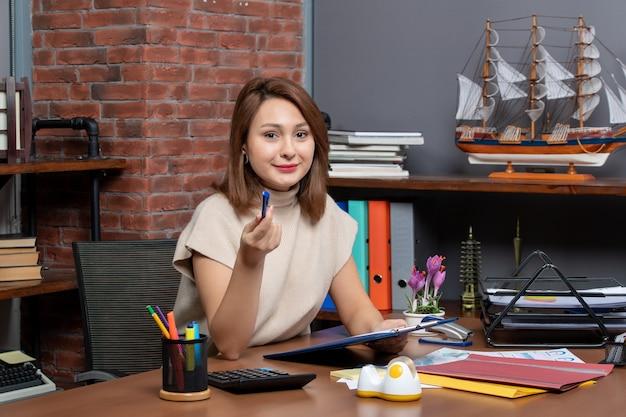 Vue de face d'une jolie femme travaillant au bureau