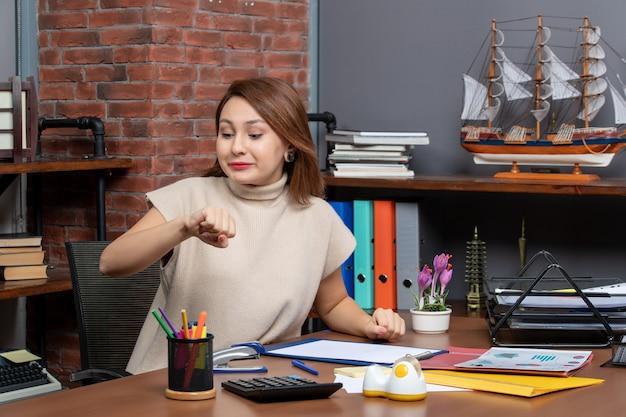 Vue de face d'une jolie femme vérifiant le temps de travail au bureau