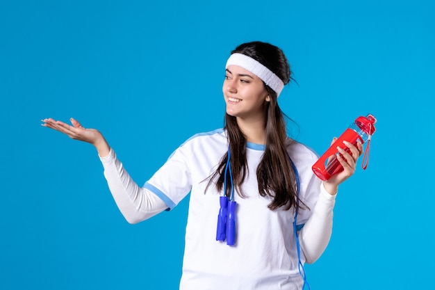 Vue de face jolie femme en vêtements de sport avec une bouteille d'eau sur bleu