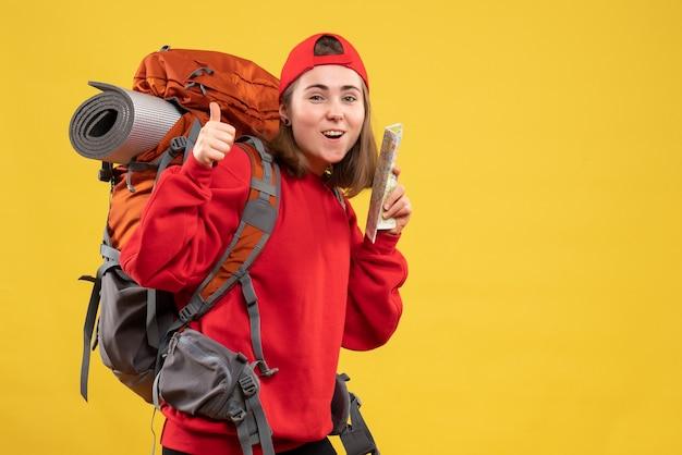 Vue de face jolie femme voyageur avec sac à dos tenant la carte gestes thumbs up sign