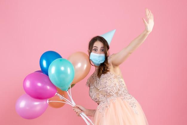 Vue de face jolie fêtarde avec chapeau de fête et masque médical tenant des ballons colorés levant la main