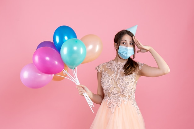 Vue de face jolie fêtarde avec chapeau de fête et masque médical tenant des ballons colorés mettant la main sur son front