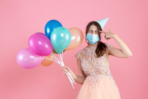 Vue de face jolie fêtarde avec chapeau de fête et masque médical tenant des ballons colorés mettant le pistolet à doigt sur sa tempe