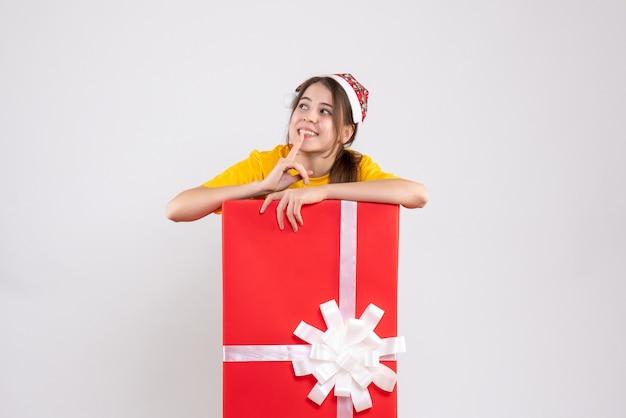 Vue de face jolie fille avec bonnet de noel debout derrière un grand cadeau de noël