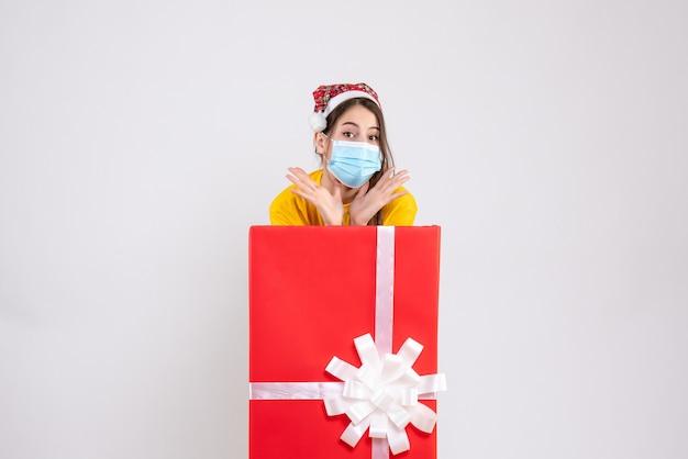 Vue de face jolie fille avec bonnet de noel et masque debout derrière un grand cadeau de noël