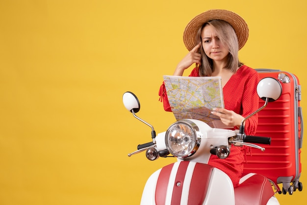Vue de face de jolie fille confuse sur cyclomoteur avec grande valise tenant la carte