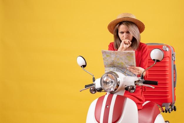 Vue de face de jolie fille confuse sur cyclomoteur avec valise rouge tenant la carte