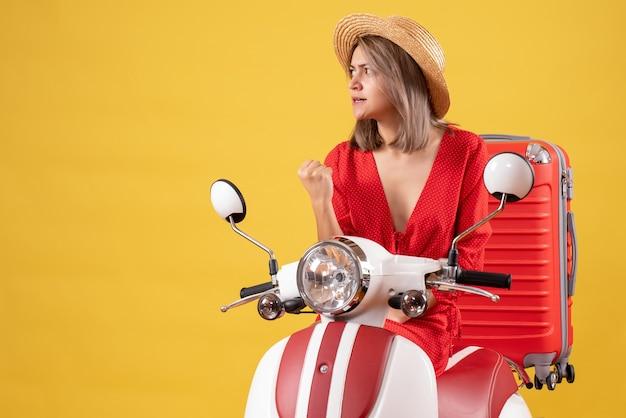 Vue de face d'une jolie fille déterminée sur un cyclomoteur avec valise rouge