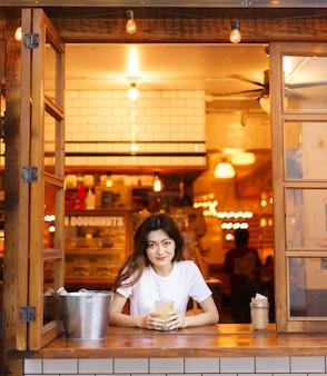 Vue de face de jolie fille japonaise buvant de la limonade