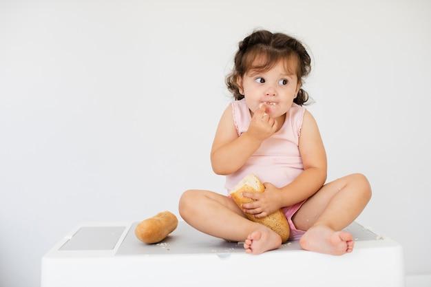 Vue de face jolie fille mangeant du pain