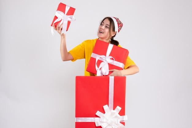 Vue de face jolie fille de noël avec bonnet de noel tenant des cadeaux debout derrière un grand cadeau de noël