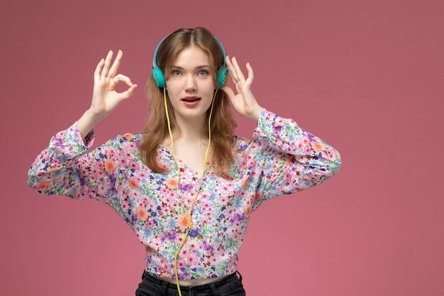 Vue de face jolie jeune femme montre que tout va bien avec ses doigts et écouter de la musique