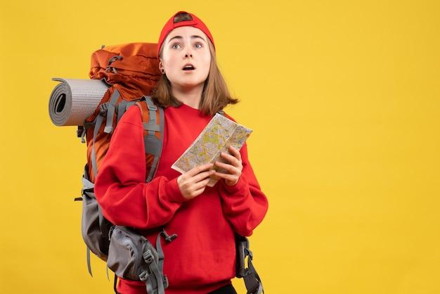 Vue de face jolie randonneuse avec sac à dos rouge tenant la carte à la recherche