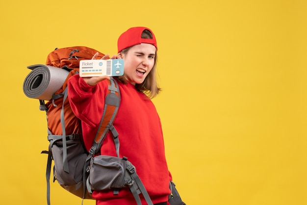 Vue de face jolie randonneuse avec sac à dos tenant billet d'avion